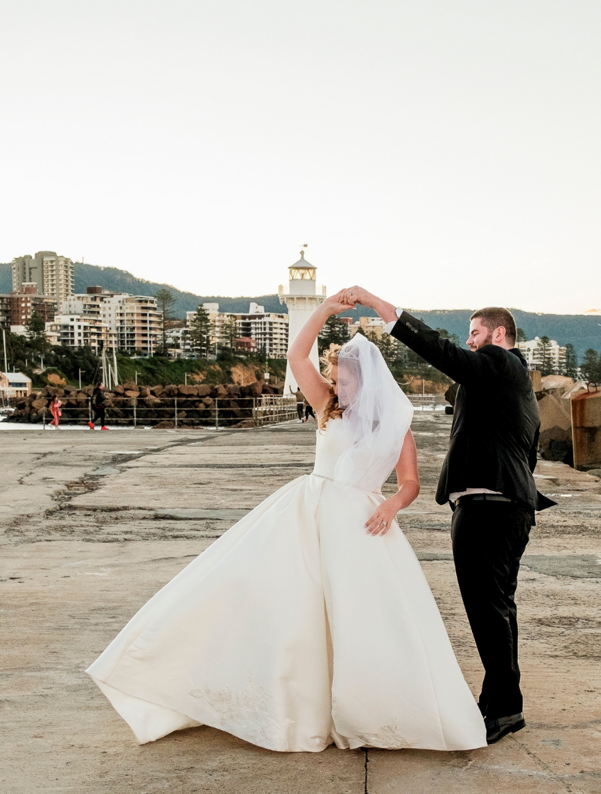 Bride and groom dancing at wollongong breakwater lighthouse