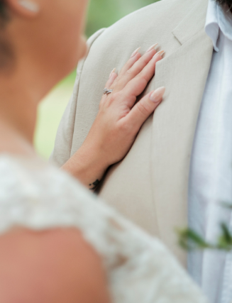 Close up brides hand on grooms chest