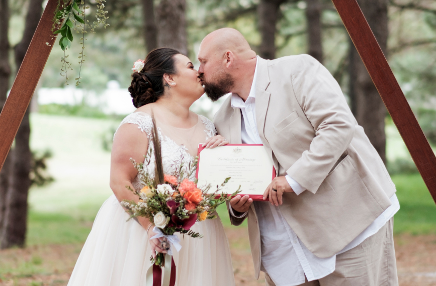 bride and groom kissing and holding marriage certificate