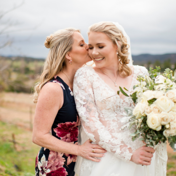 mother of the bride kissing bride