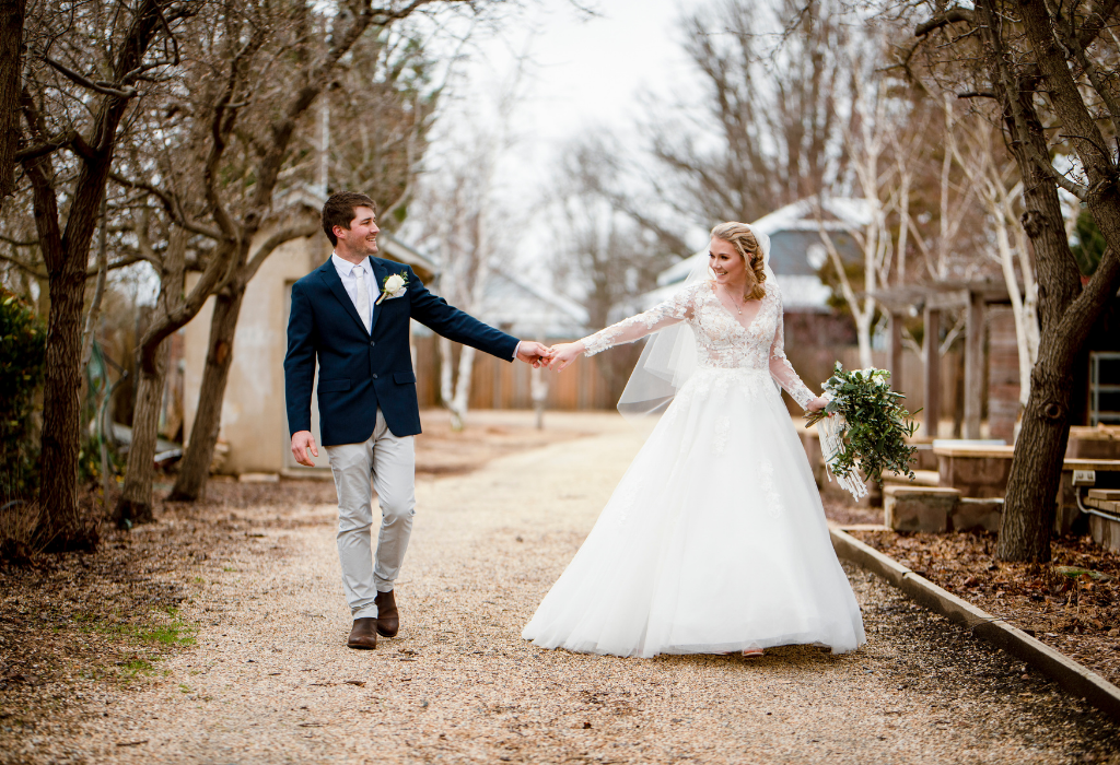 Bride and groom holding hands under winter trees