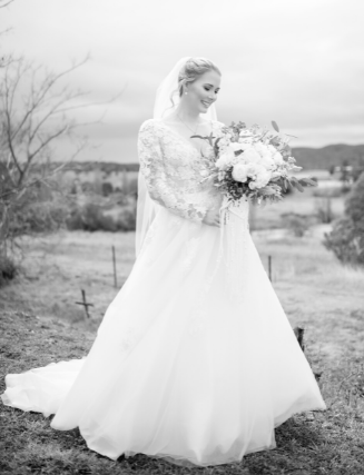 Black and white bride looking at bouquet