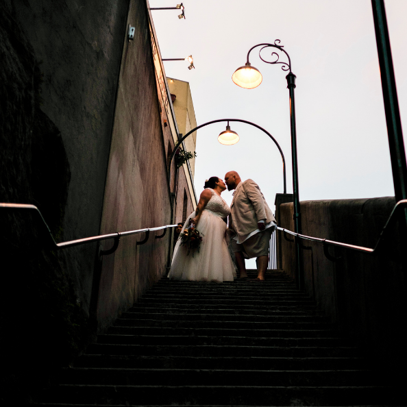 bride and groom kissing at top of stairs