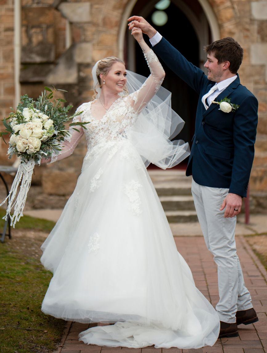 newlyweds dancing in front of church - winter wedding