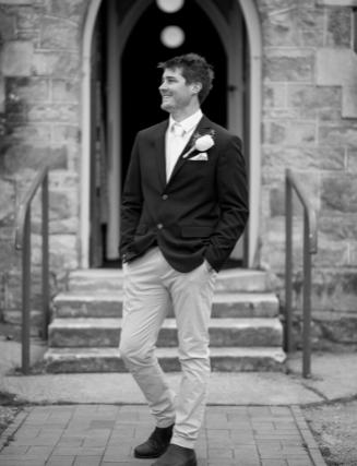 Black and white groom standing in front of church