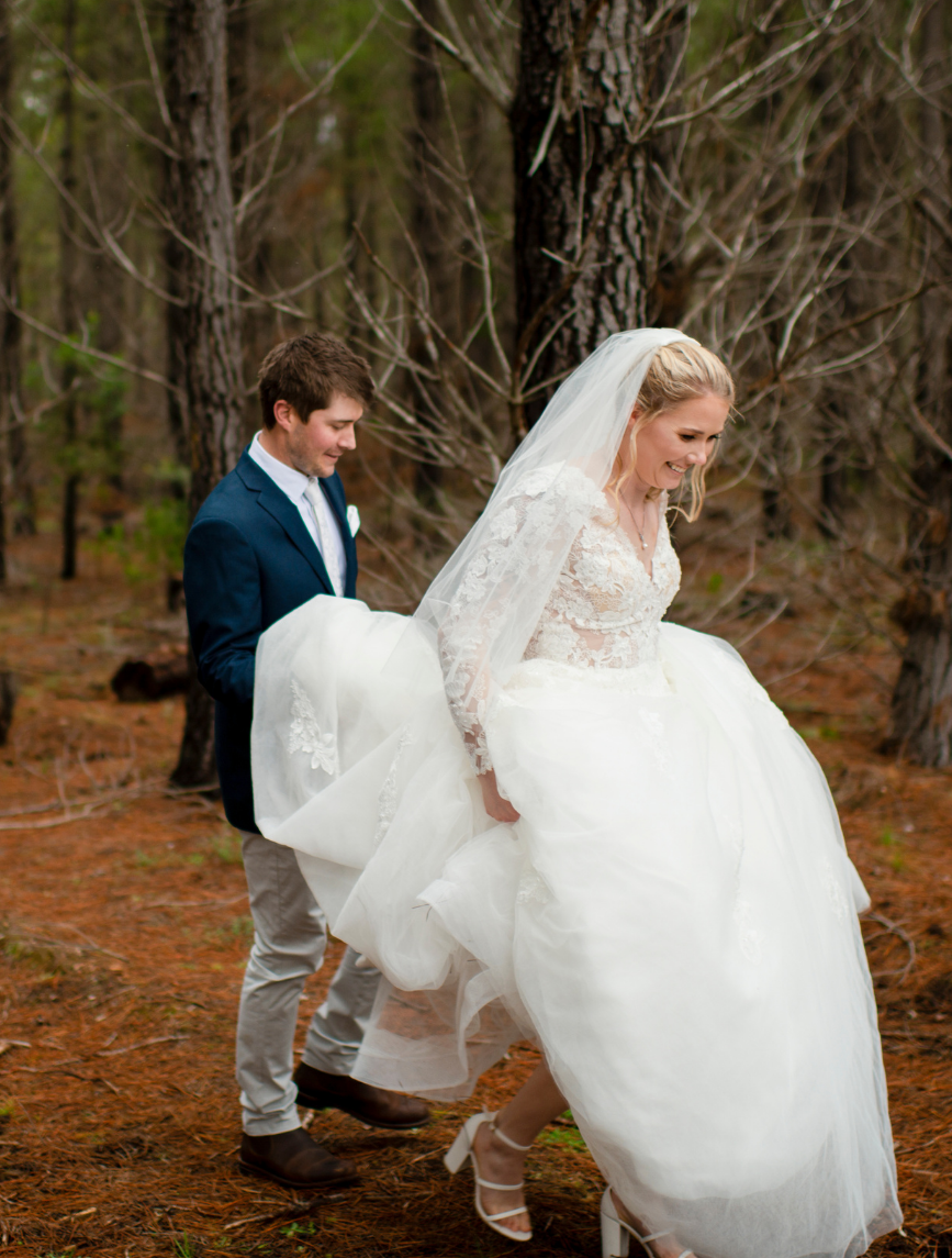 groom holding brides dress while walking through forest in winter