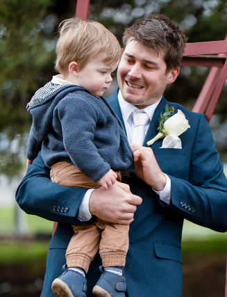 Groom in navy suit holding son