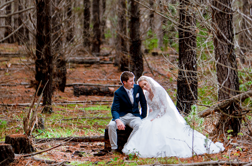 bride leaning on groom while sitting in forest in winter
